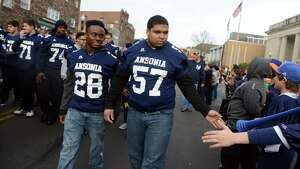 Ansonia High School football players Hugh Jackson (28) and Antone Mack (57) march down Main Street with the rest of the Chargers, and Ansonia Youth cheerleaders, AYC National Championship winners and runners-up, Saturday, Dec. 21, 2013 during a parade in their honor in downtown Ansonia, Conn.