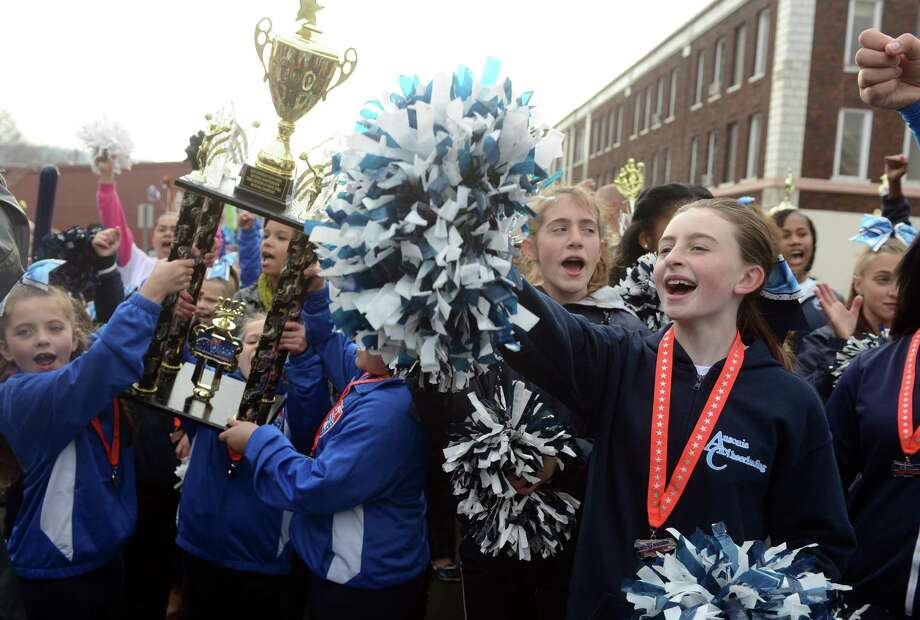 Lexi Rogers cheers Saturday, Dec. 21, 2013 during a parade to honor Class S state football champions, the Ansonia Chargers, and Ansonia Youth cheerleaders, AYC National Championship winners and runners-up. Photo: Autumn Driscoll / Connecticut Post