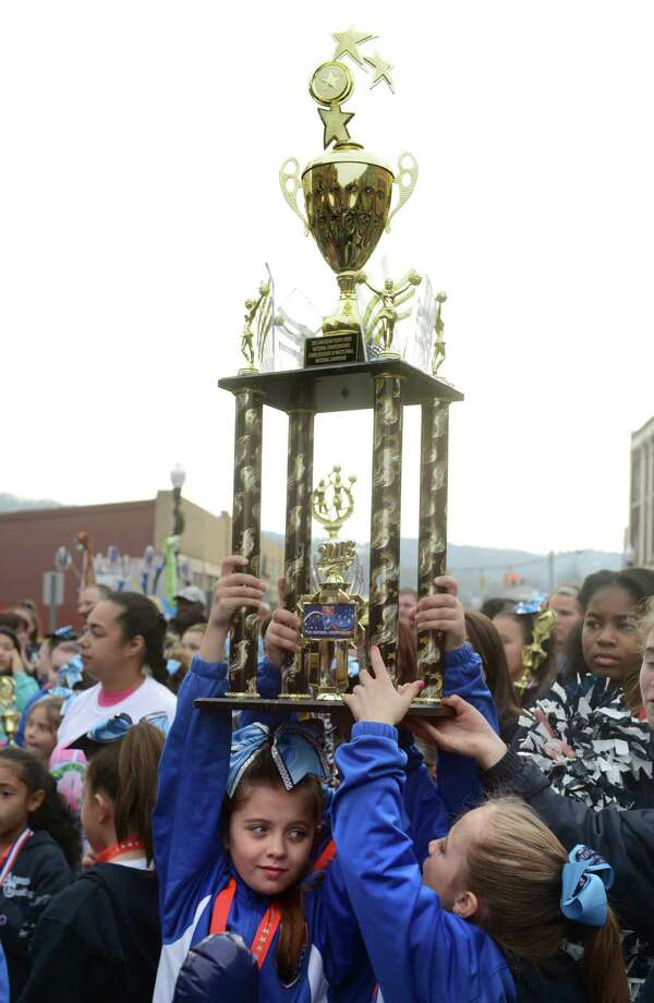 Makayla Cavalaro, 8, left, and Aubrey Moity, 8, hold up their division 10 national championship trophy Saturday, Dec. 21, 2013 during a parade to honor Class S state football champions, the Ansonia Chargers, and Ansonia Youth cheerleaders, AYC National Championship winners and runners-up Saturday, Dec. 21, 2013. Photo: Autumn Driscoll / Connecticut Post