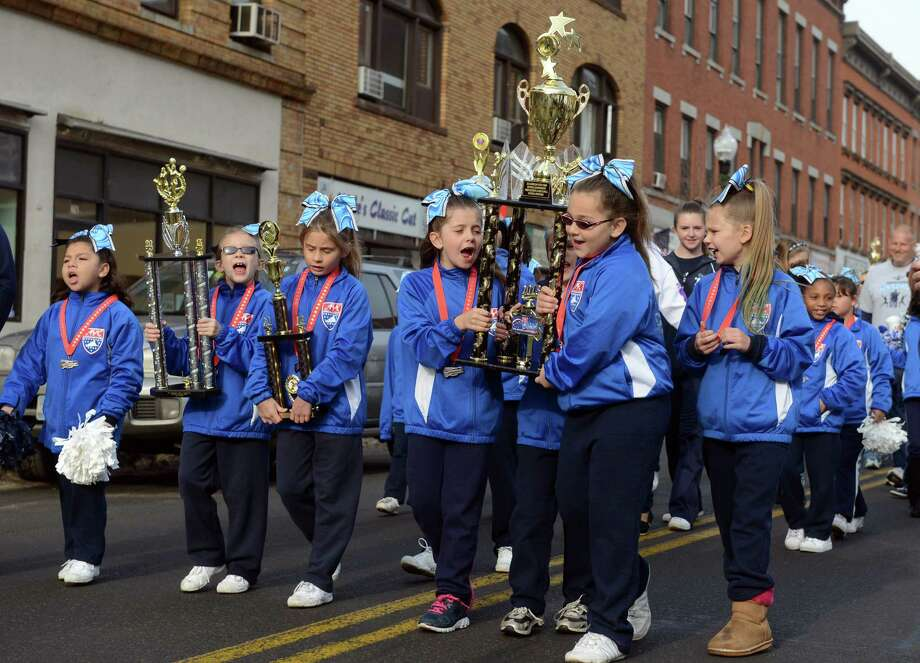 Division 10 cheerleaders march with their national championship trophy Saturday, Dec. 21, 2013 during a parade to honor Class S state football champions, the Ansonia Chargers, and Ansonia Youth cheerleaders, AYC National Championship winners and runners-up Saturday, Dec. 21, 2013. Photo: Autumn Driscoll / Connecticut Post