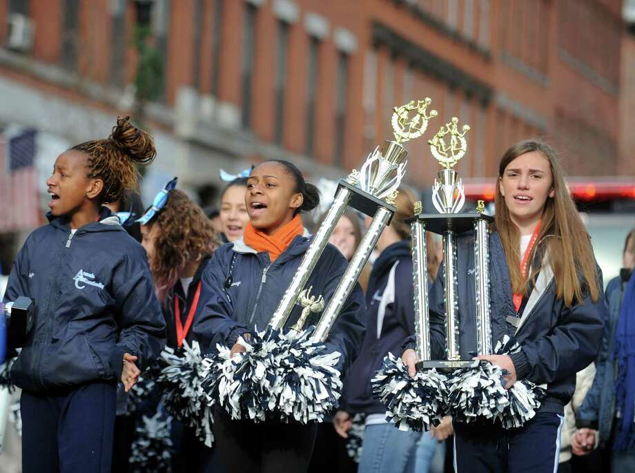 Asjha Jones, Tamaya Upchurch and Payton Westine carry their trophies Saturday, Dec. 21, 2013 during a parade to honor Class S state football champions, the Ansonia Chargers, and Ansonia Youth cheerleaders, AYC National Championship winners and runners-up, Saturday, Dec. 21, 2013 through downtown Ansonia, Conn. Photo: Autumn Driscoll / Connecticut Post