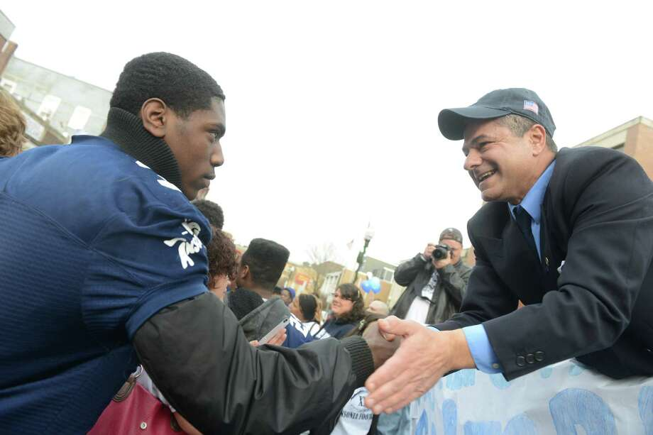 Ansonia High School football player Saiheed Sanders shakes hands with mayor David S. Cassetti Saturday, Dec. 21, 2013 during a parade to honor Class S state football champions, the Ansonia Chargers, and Ansonia Youth cheerleaders, AYC National Championship winners and runners-up Saturday, Dec. 21, 2013. Photo: Autumn Driscoll / Connecticut Post