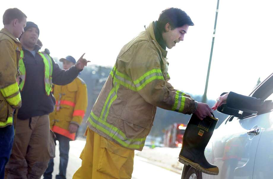 Seymour junior firefighter Ethan Iott, 14, collects money from a motorist on Derby Avenue Saturday, Dec. 21, 2013 during a boot drive.  Seymour police, fire and ambulance departments joined together for the drive to raise money for Nina Poeta, the 16-year old Seymour High School cheerleader battling a brain tumor. Photo: Autumn Driscoll / Connecticut Post