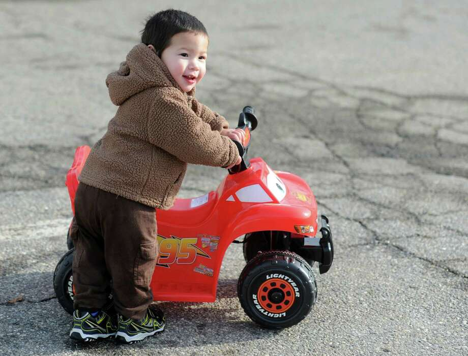 Sixteen-month-old Joshua Phill, of Ansonia, enjoys the wide-open road of the Nolan Field parking lot to test his new wheels Saturday, Dec. 21, 2013 in Ansonia, Conn. Photo: Autumn Driscoll / Connecticut Post