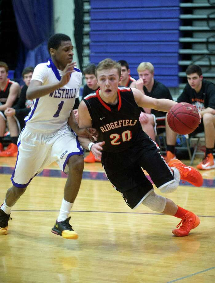 Ridgefield's Matthew Brennan controls the ball as he is defended by Westhill's Jeremiah Livingston during Friday's basketball game in Stamford, Conn., on December 20, 2013. Photo: Lindsay Perry / Stamford Advocate