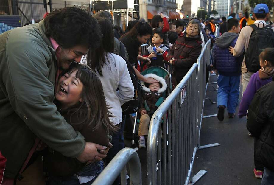 Shaeleigh McAllister, 7, gets a hug from her father, Paul Smith, as they wait in line at Glide. Photo: Leah Millis, The Chronicle