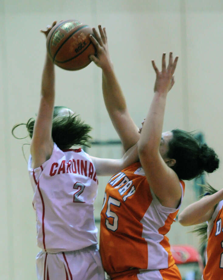 At right, Kayla Handberry (# 25) of Danbury blocks the shot of Caroline Beneville (# 2) of Greenwich during the girls high school basketball game between Greenwich High School and Danbury High School at Greenwich, Friday night, Dec. 20, 2013. Photo: Bob Luckey / Greenwich Time