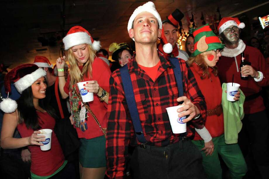 Jimmy Paley of Saratoga Springs, center, joins the party as revelers listen to live music during SantaCon on Saturday, Dec. 21, 2013, at Putnam Den in Saratoga Springs, N.Y. The pub crawl aims to collect canned goods for the Franklin Community Center food pantry. (Cindy Schultz / Times Union) Photo: Cindy Schultz / 00025127A
