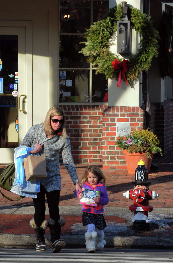 Molly Patton and her daughter Sydney, 3, cross Post Road while doing some Christmas shopping in downtown Fairfield, Conn. on Saturday December 21, 2013. Photo: Christian Abraham / Connecticut Post