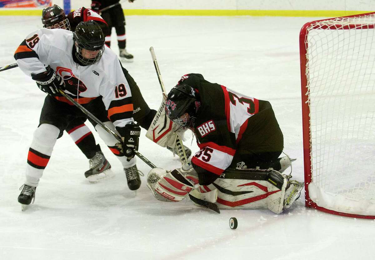 Branford's Adolph Brink guards the goal as Stamford's Tim Walsh competes for control of the puck during Saturday's hockey game against Branford at Terry Connors Rink in Stamford, Conn., on December 21, 2013.