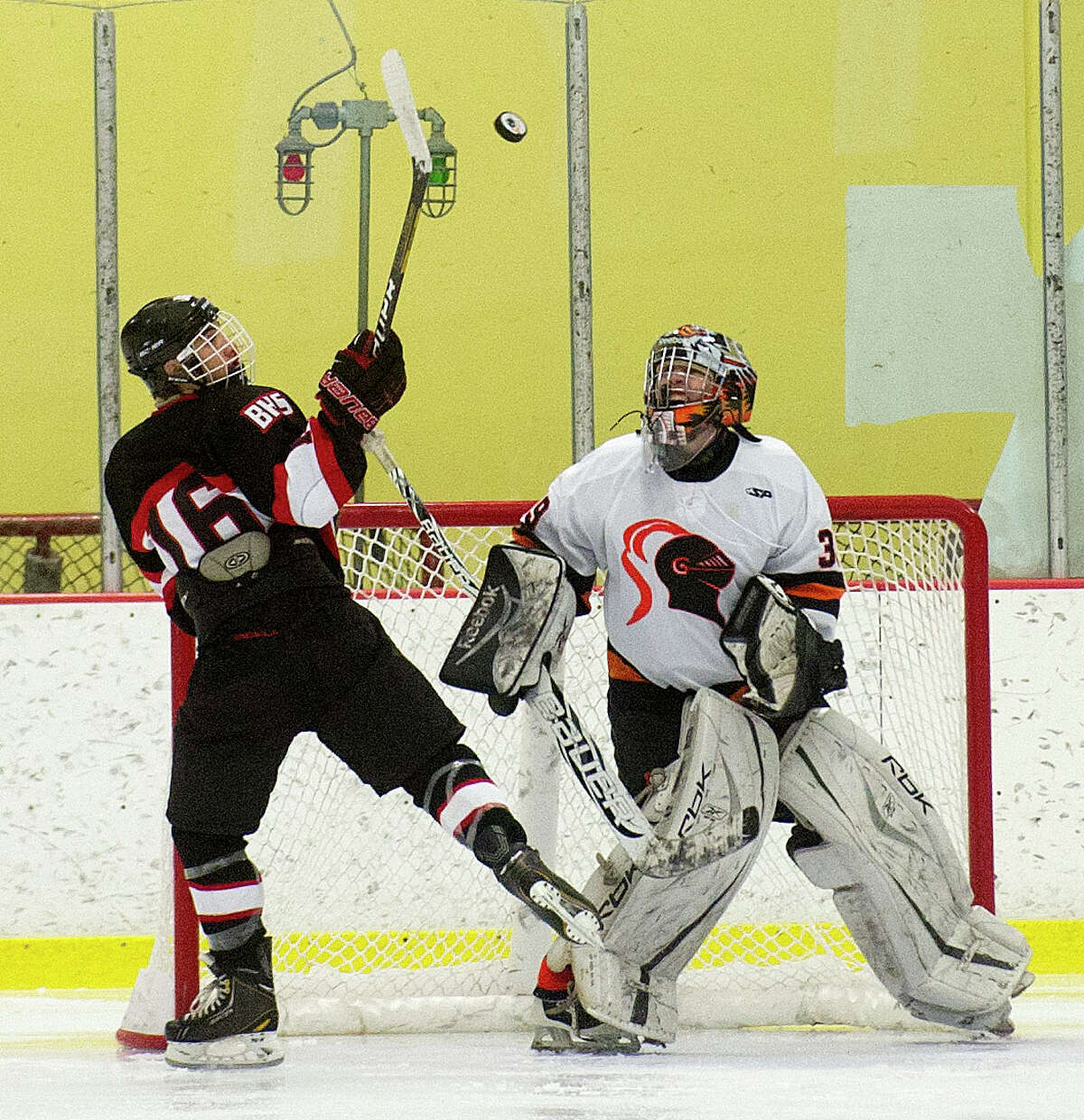 Stamford goalie Devin Camlin and Branford's Jason Vitale watch the puck in the air during Saturday's hockey game against Branford at Terry Connors Rink in Stamford, Conn., on December 21, 2013.
