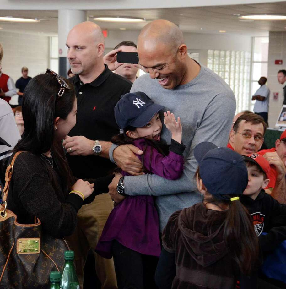Six-Year-Old Chloe Chin from Rockland County gives New York Yankees pitching great Mariano Rivera a big hug as he gives her one in return. Rivera spoke at a fundraiser at Ridgefield High School on Saturday Dec. 21,2013. Photo: Lisa Weir / The News-Times Freelance