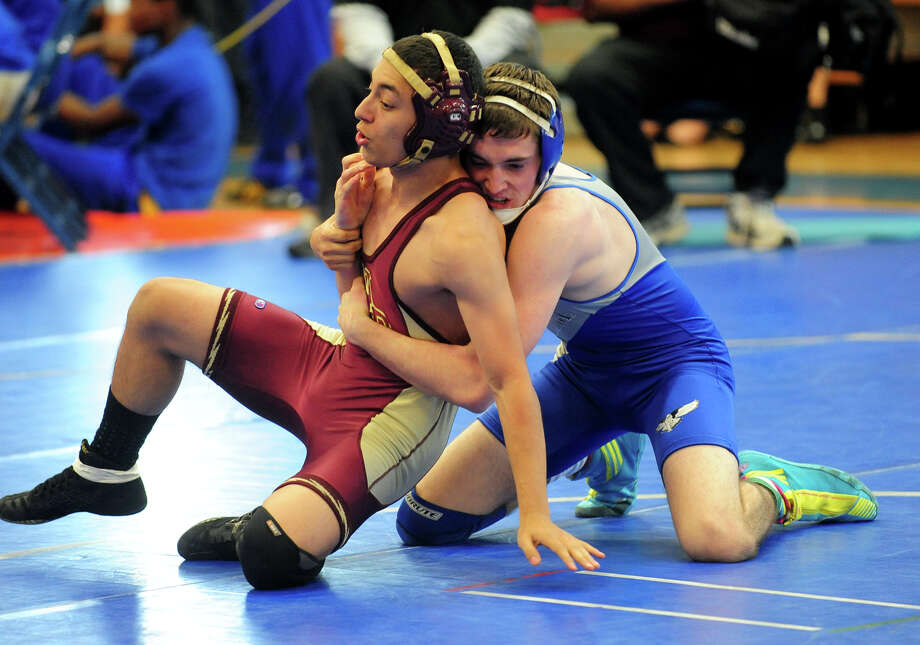 Fairfield Ludlowe's Austin Reid, in blue, goes up against New Britain's Alfred Rivera, during wrestling action in Fairfield, Conn. on Saturday December 21, 2013. Photo: Christian Abraham / Connecticut Post