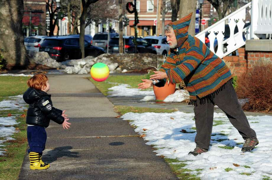 Neil Golder, of Fairfield, plays catch with family friend Marco Gaudio, 2, on Sherman Green in downtown Fairfield, Conn. on Saturday December 21, 2013. Photo: Christian Abraham / Connecticut Post