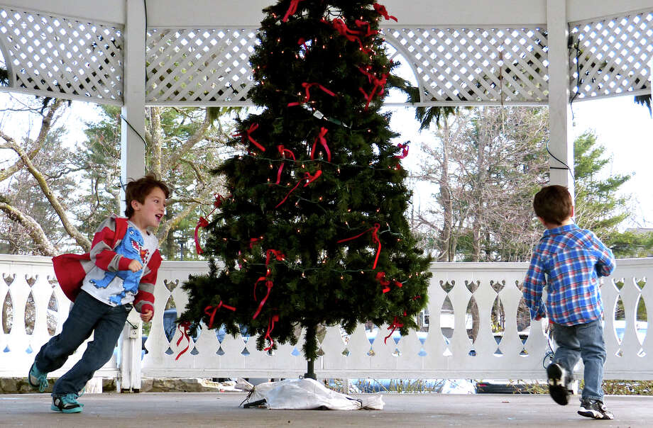 Sacha Kerner, 6, runs around the Christmas tree chasing his brother Jonah, 4, right, in the gazeebo on Sherman Green in downtown Fairfield, Conn. on Saturday December 21, 2013. Photo: Christian Abraham / Connecticut Post