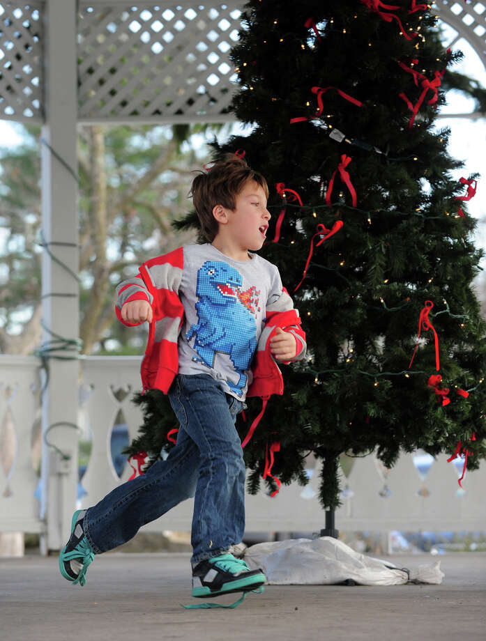 Sacha Kerner, 6, runs around the Christmas tree in the gazeebo on Sherman Green in downtown Fairfield, Conn. on Saturday December 21, 2013. Photo: Christian Abraham / Connecticut Post