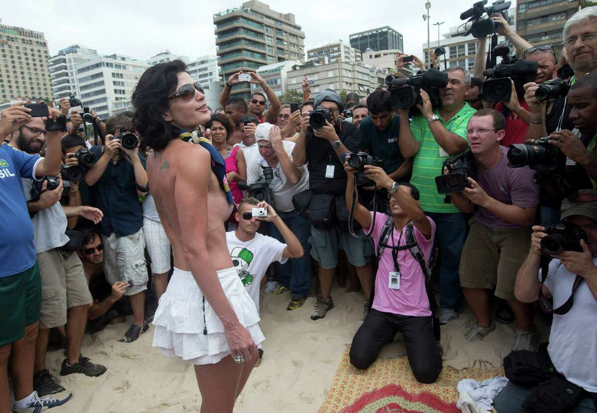 A woman poses for photos during a protest against a topless ban on the Ipanema beach, in Rio de Janeiro, Brazil, Saturday, Dec. 21, 2013. A much-hyped protest for the right to go topless on Rio de Janeiro's beaches fell flat Saturday when only a handful of women bared their chests for the movement. Under Brazil's penal code, which dates back to the 1940s, female toplessness is an