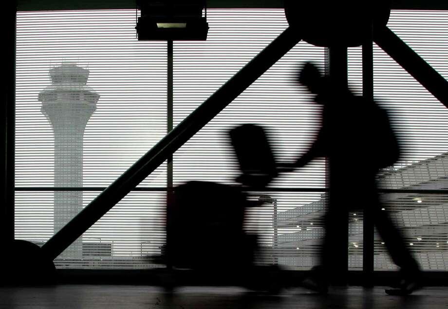 A traveler walks through Terminal 3 at O'Hare International Airport in Chicago on Saturday, Dec. 21, 2013. The National Weather Service issued a hazardous weather outlook for north central Illinois, northeast Illinois and northwest Indiana Saturday morning. (AP Photo/Nam Y. Huh) Photo: Nam Y. Huh, STF / AP