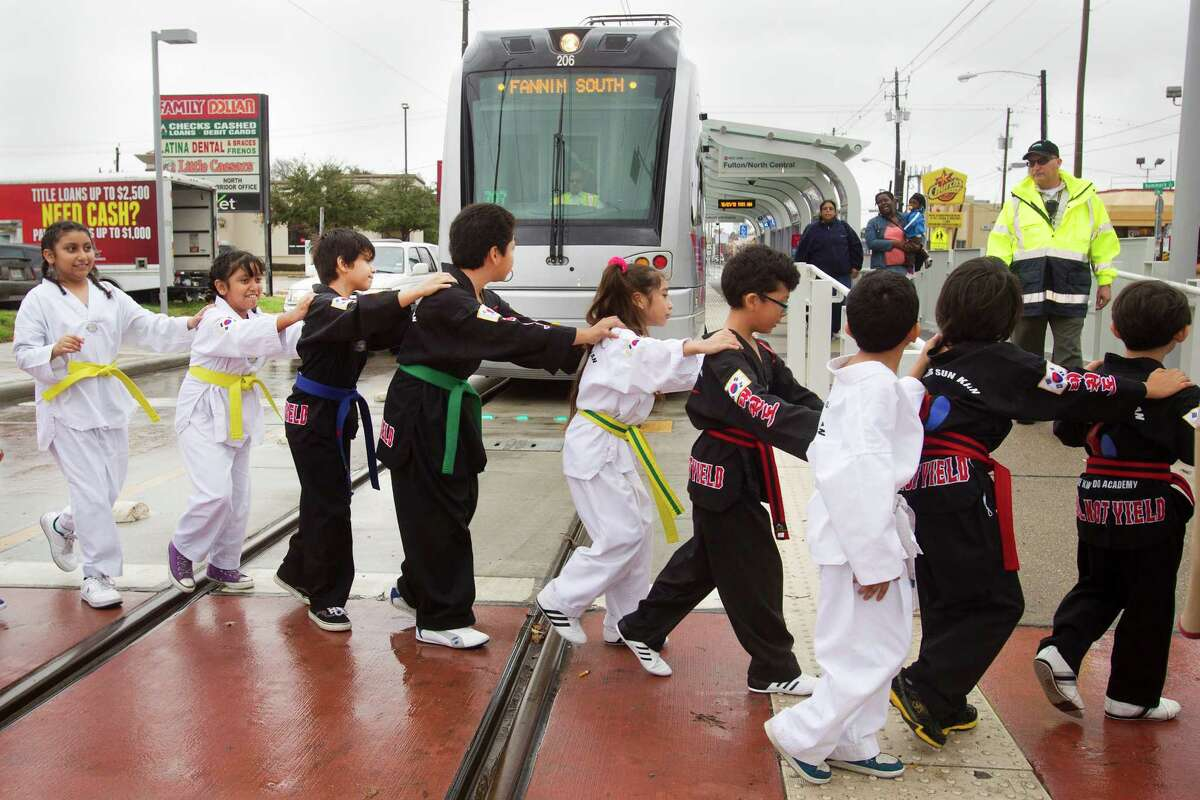 Martial arts students cross the Red Line tracks at the Fulton/North Central Station during the new section's opening Saturday.