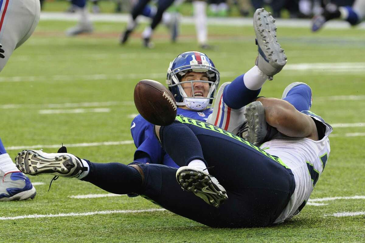 Seattle Seahawks defensive end Michael Bennett, bottom, forces a fumble off New York Giants quarterback Eli Manning during the second half of an NFL football game on Sunday, Dec. 15, 2013, in East Rutherford, N.J. The Giants recovered their fumble on the play. (AP Photo/Bill Kostroun) ORG XMIT: ERU117