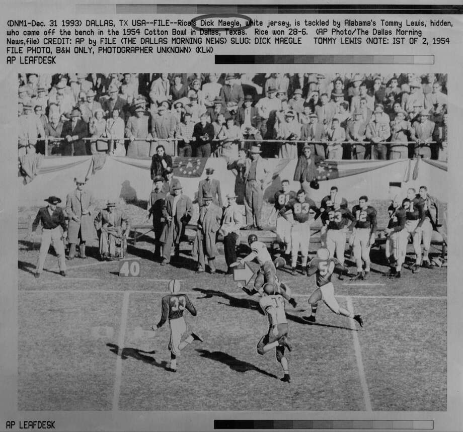 One of the most famous plays in history took place in the 1954 Cotton Bowl when Rice's Dick Maegle, center in white jersey, was tackled by Alabama's Tommy Lewis, who came off the bench. A 95-yard TD was awarded. / AP
