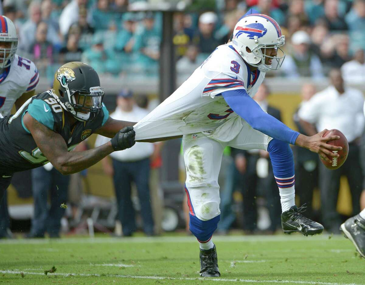 Jacksonville Jaguars defensive end Andre Branch (90) grabs Buffalo Bills quarterback EJ Manuel (3) by the jersey to stop him during the first half of an NFL football game in Jacksonville, Fla., Sunday, Dec. 15, 2013.(AP Photo/Phelan M. Ebenhack) ORG XMIT: JVS110