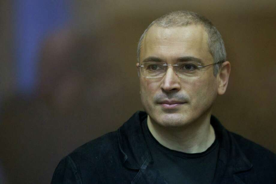 FILE - In this Wednesday, Dec. 29, 2010 file photo Mikhail Khodorkovsky stands behind a glass enclosure at a court room in Moscow, Russia. President Vladimir Putin says he will pardon jailed oil tycoon Mikhail Khodorkovsky after more than a decade in prison. Putin told reporters after his marathon news conference Thursday Dec. 19, 2013, that Khodorkovsky submitted an appeal for pardon and he intends to grant it. (AP Photo/Misha Japaridze, File) Photo: Misha Japaridze, STF / AP