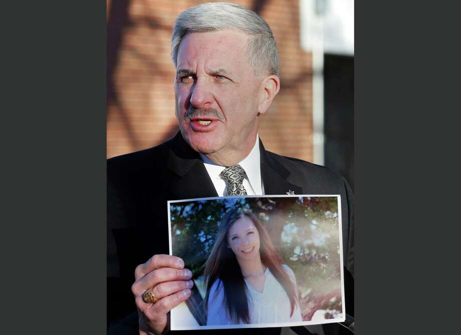 FILE - In this Saturday, Dec. 14, 2013, file photo, Arapahoe County Sheriff Grayson Robinson holds a picture of Claire Davis, the 17-year-old student who was shot in the head by a classmate, during a briefing at Arapahoe High School in Centennial, Colo. Hospital officials said in a statement Saturday, Dec. 21, 2013, that Davis has died. (AP Photo/Ed Andrieski, File) Photo: Ed Andrieski, STF / AP