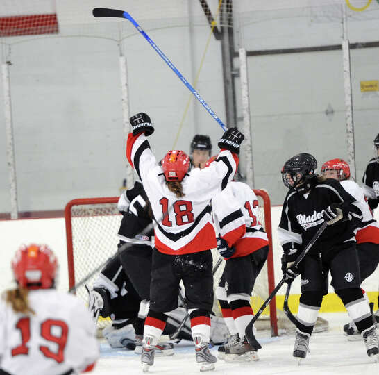 At center, Lizzie Russell (# 18) of Greenwich raises her stick in celebration after scoring a first