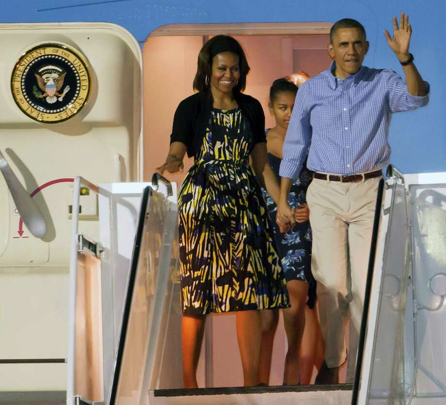 President Barack Obama, right, and first lady Michelle Obama, left, along with their daughter Sasha, center back, disembark Air Force One after arriving at Joint Base Pearl Harbor-Hickam for their family Christmas vacation, Friday, Dec. 20, 2013, in Honolulu. The first family will be spending their vacation in Hawaii and return to Washington on Jan. 5, 2014. (AP Photo/Eugene Tanner) Photo: Eugene Tanner, FRE / FR168001 AP