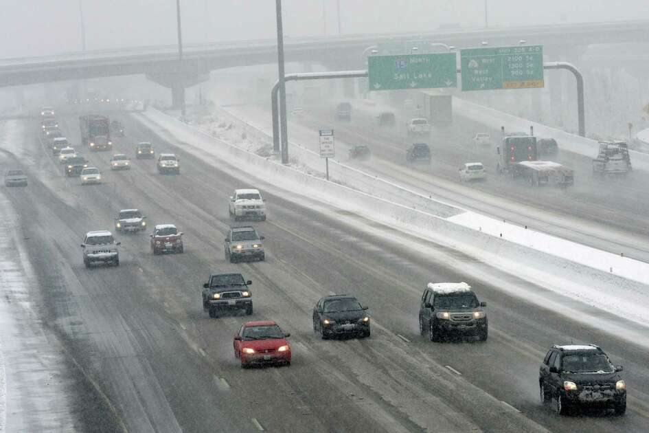 Traffic moves slowly along I-15 at 2700 South during the heavy wet snow falling Thursday, Dec. 19, 2013 in Salt Lake City. A winter storm blasted northern Utah on Thursday, causing power outages, dozens of traffic accidents and the temporary shutdown of Salt Lake's airport after a cargo plane slipped on a runway. (AP Photo/The Salt Lake Tribune, Al Hartmann)  DESERET NEWS OUT; LOCAL TV OUT; MAGS OUT