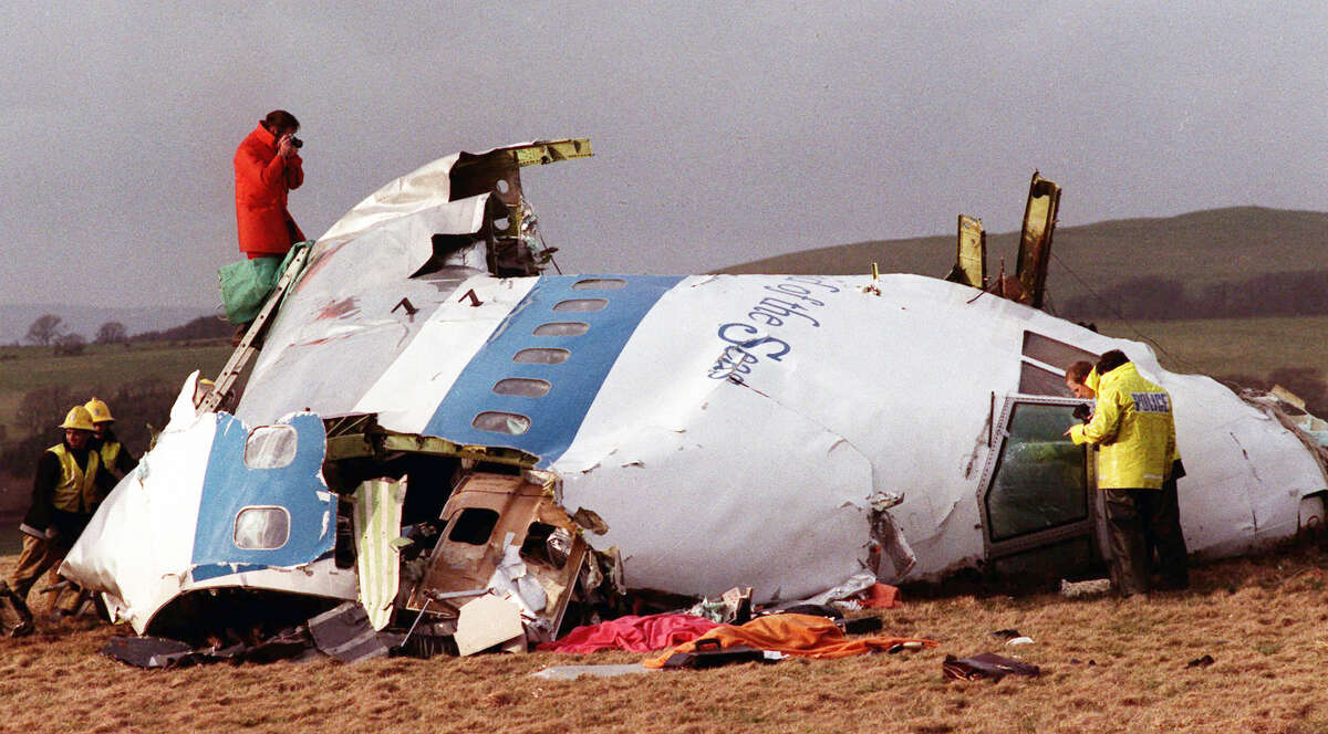 This Dec. 22, 1988, file photo shows police and investigators looking at what remains of the flight deck of Pan Am 103 on a field in Lockerbie, Scotland.