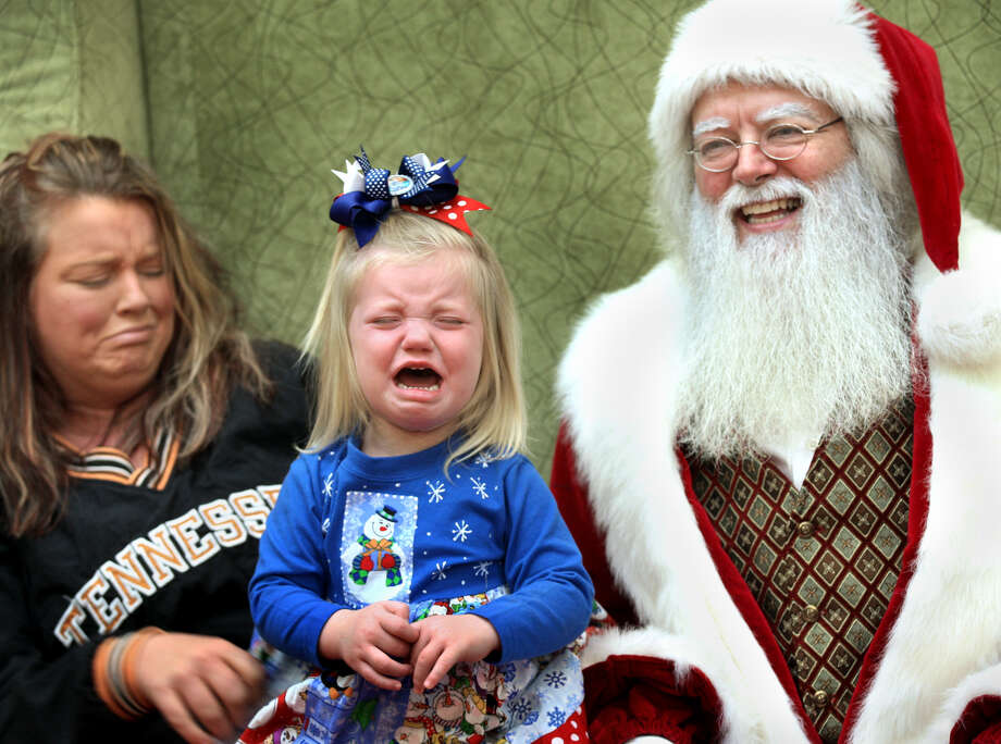 Two-year-old Emma Williams, of Front Royal, Va., center, does not appear to enjoy meeting with Santa Claus, portrayed by Charles Van Nort of Baltimore, while visiting Apple Blossom Mall in Winchester, Va. her mother, Rhonda, Friday, Dec. 20, 2013. Photo: Jeff Taylor, Associated Press / The Winchester Star