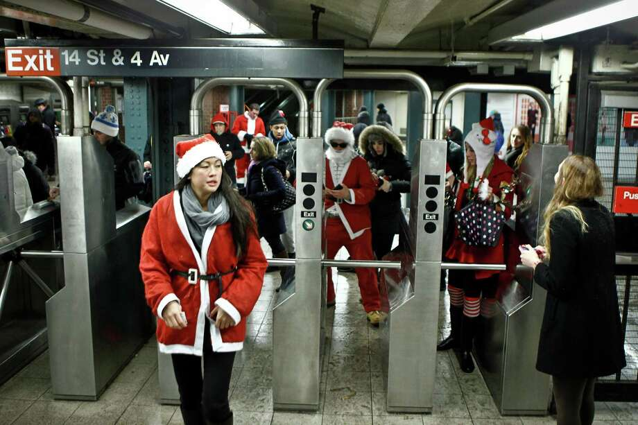Revelers dressed as Santa Claus enter the 14th street subway station during the annual SantaCon bar crawl event on December 14, 2013 in New York City. The SantaCon annual event occurs worldwide in more than 300 cities in 44 countries. Photo: Kena Betancur, Getty Images / 2013 Getty Images