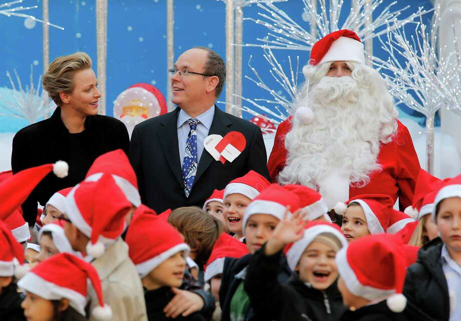 Prince Albert II of Monaco, center, with his wife Princess Charlene and a man dressed in a Santa Claus costume, pose for photographers as they welcome Monaco's children for the traditional Christmas tree viewing and present receiving session at Monaco palace, Wednesday, Dec. 18, 2013. This event takes place every years ahead of christmas. Photo: Lionel Cironneau, Associated Press / AP