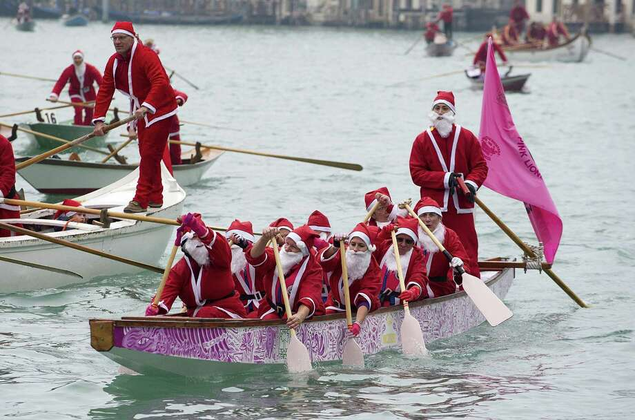 Rowers dressed in Santa Claus costumes take part in the Christmas Regatta on the Grand Canal on December 21, 2013 in Venice, Italy. The Christmas Regatta now in it's 4th year is an event organised by University of Ca Foscari. Photo: Marco Secchi, Getty Images / 2013 Getty Images
