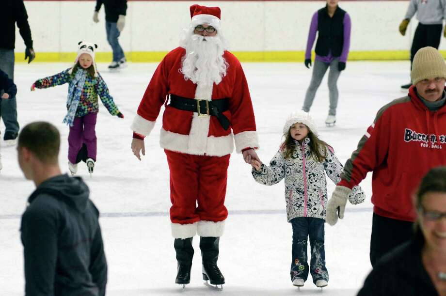 Patrick Schamburek, dressed as Santa Claus, center, skates with his daughter Miley, 5, on Saturday, Dec. 21, 2013 during the santa Skate event at the Manitowoc County Ice Center in Manitowoc, Wis. Photo: Matthew Apgar, Associated Press / Herald Times Reporter/HTR Media