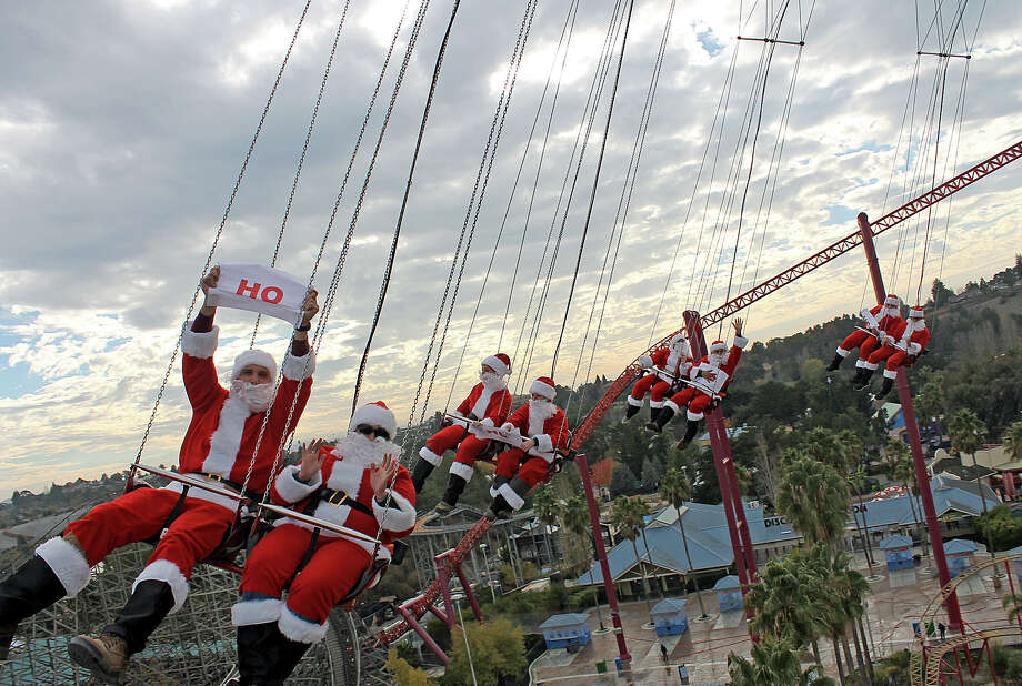 In this Dec. 18, 2013 photo released by Six Flags Discovery Kingdom, 32 men dressed as Santa Claus ride the 150-foot tall SkyScreamer tower swing ride at Six Flags Discovery Kingdom in Vallejo, Calif. The park, in conjunction with two Six Flags parks in Texas, each loaded Santa passengers – 88 in total - on their SkyScreamer rides to celebrate the holiday season. Photo: Jason Quintos, Associated Press / Six Flags Discovery Kingdom