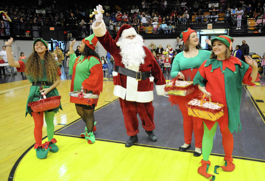 A man dressed as Santa Claus, center, and four women dressed as elves, wave to the crowd during the 98th annual Goodfellows Christmas Party at the Sportscenter in Owensboro, Ky., on Saturday, Dec. 21, 2013. Photo: John Dunham, Associated Press / The Messenger-Inquirer