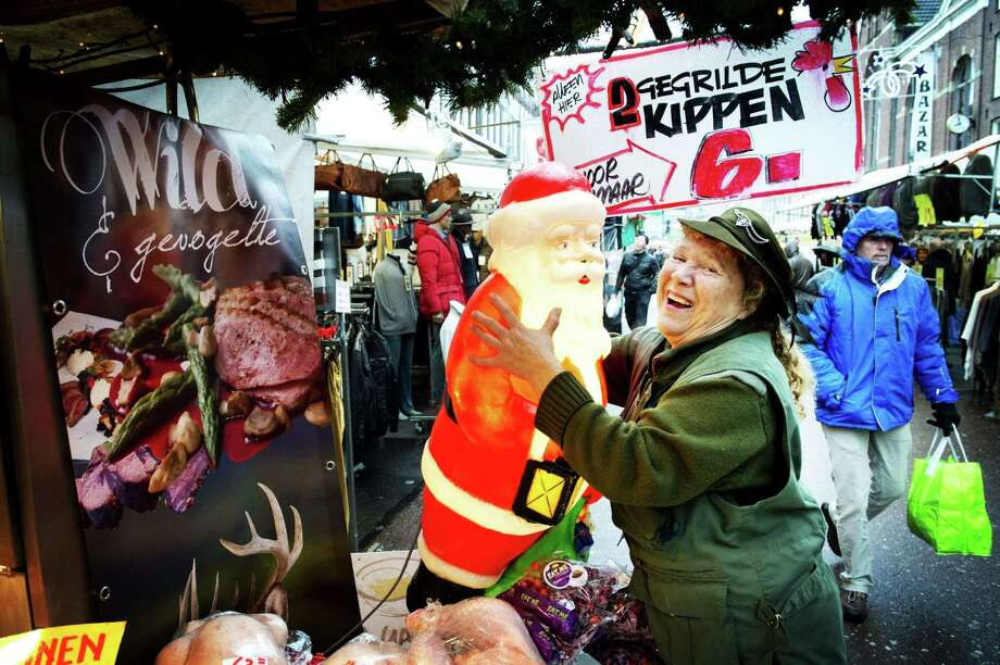 A woman embrasses a plastic Santa Claus figure at the Albert Cuypmarkt in Amsterdam during the last weekend before Christmas, in the Netherlands, on December 21, 2013. Retailers expect that the Dutch this year despite the economic crisis will spend a record amount on Christmas shopping. Photo: ROBIN UTRECHT, AFP/Getty Images / AFP
