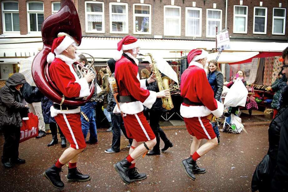 Men dressed as Santa Claus play music at the Albert Cuypmarkt in Amsterdam during the last weekend before Christmas, in the Netherlands, on December 21, 2013. Retailers expect that the Dutch this year despite the economic crisis will spend a record amount on Christmas shopping. Photo: ROBIN UTRECHT, AFP/Getty Images / AFP