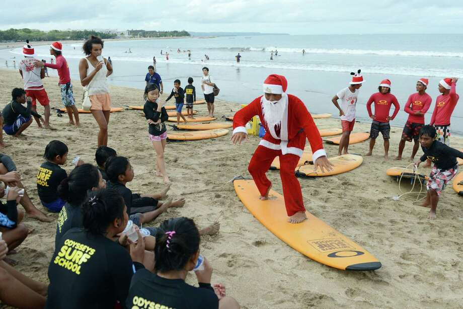 A Balinese surfer dressed in a Santa Claus outfit trains orphan children before they surf on Kuta beach near Denpasar on Indonesia's tourist island of Bali on December 21, 2013.  The popular resort island, a pocket of Hindu culture in a  country with the biggest Muslim population in the world, receives thousands of tourists every year over the Christmas season. Photo: SONNY TUMBELAKA, AFP/Getty Images / AFP