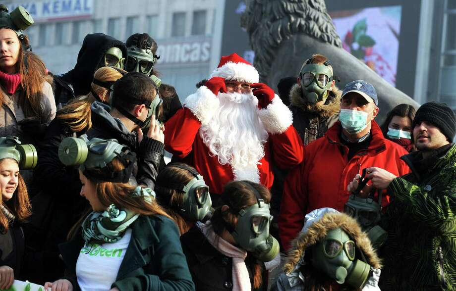 A man dressed as Santa Claus stands among a group of protesters wearing gas masks as they take part in a demonstration rally to draw attention to the problem of atmospheric pollution in Skopje on December 21, 2013. For more than a week, Skopje and three other Macedonian cities have been stifled by air pollution caused mainly by traffic, and wood and oil-burning heating systems. The government recently imposed emergency measures to protect the population, instructing private companies and state institutions in the four cities to let pregnant woman and employees over the age of 60 stay at home. Photo: ROBERT ATANASOVSKI, AFP/Getty Images / AFP