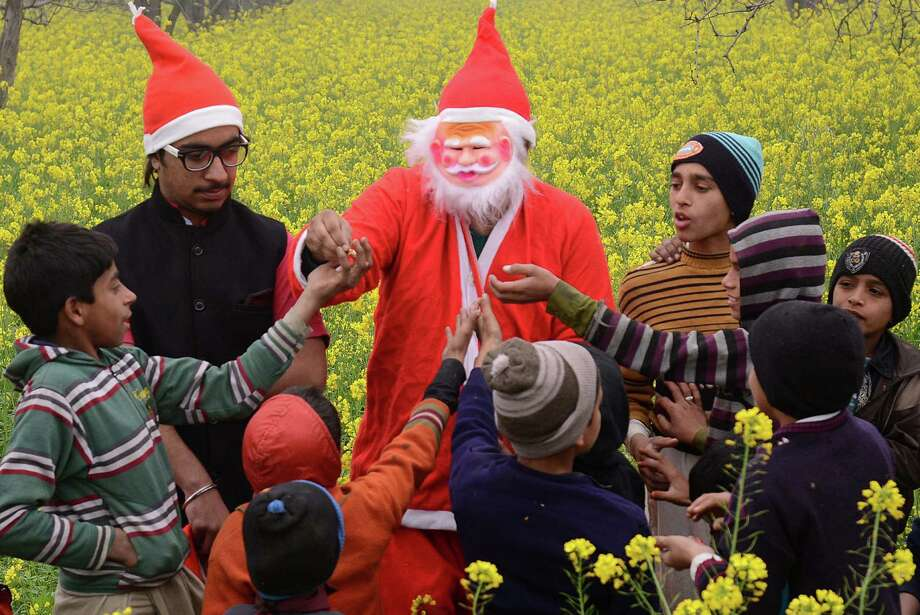 An Indian resident dressed as Santa Claus poses as he distributes sweets to children in a village on the outskirts of Amritsar on December 21, 2013. Despite Christians forming a little over 2 percent of the billion plus population in India, with Hindus comprising the majority, Christmas is celebrated with much fanfare and zeal throughout the country. Photo: NARINDER NANU, AFP/Getty Images / AFP