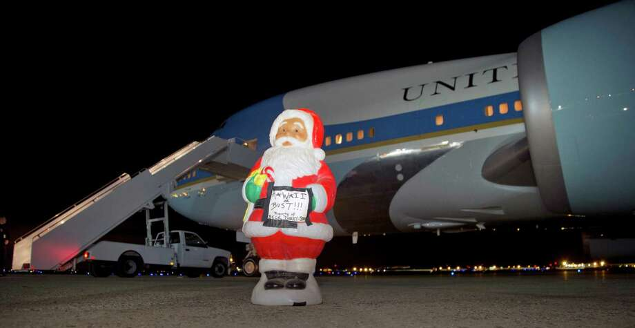 "A Santa figurine with a sign that says ""Hawaii or Bust"" stands on the tarmac in front of Air Force One before President Barack Obama and first lady Michelle Obama and their daughters Sasha and Malia board, Friday, Dec. 20, 2013, in Andrews Air Force Base, Md., en route to Hawaii for their annual family vacation. A staff member put the stature there to photograph it before departure. Photo: Carolyn Kaster, Associated Press / AP"