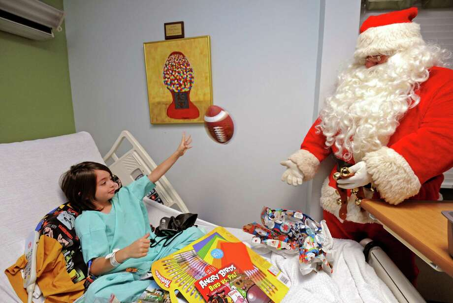 Kennedy University Hospital patient Sebastian Amwake, 8, plays with Santa Claus with a football he received from D.J. Alexis in Washington Township, N.J., on Friday, Dec. 20, 2013. Alexis, 11, handed out hundreds of toys at the hospital on Friday. D.J. collected the toys in memory of his late infant brother, Emanuel, who was born prematurely and died at Kennedy in 2006. Photo: April Saul, Associated Press / The Philadelphia Inquirer