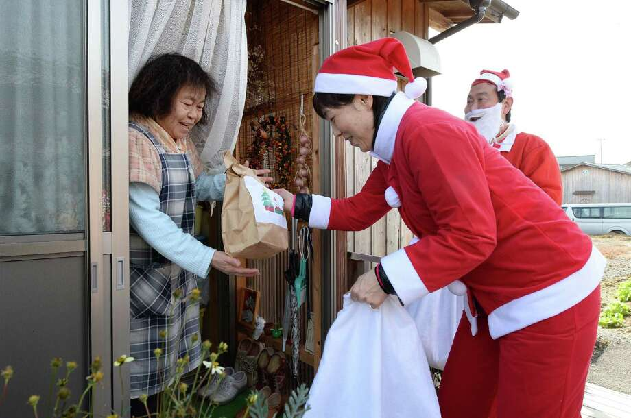 Clad in Santa Claus costumes, volunteers hand Christmas gifts to an elderly woman, who is sheltering from Narahamachi after the accident of a nulcear power plant, in Iwaki, Fukushima Prefecture, on December 21, 2013.  Some 100 volunteers delivered Christmas gifts to cheer people living at temporary housings. Photo: TORU YAMANAKA, AFP/Getty Images / AFP