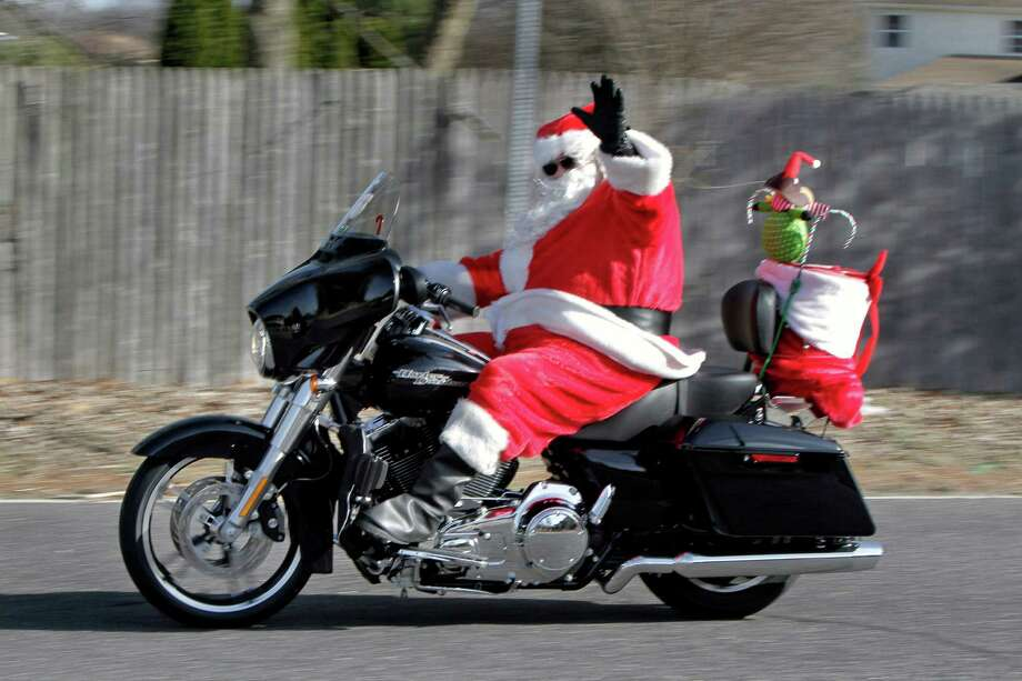 "In this Dec. 18, 2013 photo, Santa Claus waves while riding his motorcycle in Washington Twp., in N.J. Santa, who is actually ""Vic"" stopped to say hello to the road crew that was working on Egg Harbor Rd at Trent Rd. Photo: Elizabeth Robertson, Associated Press / The Philadelphia Inquirer"