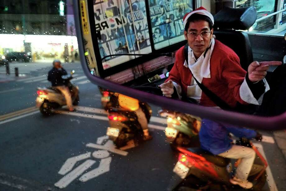 Reflected in a mirror, a public bus driver dressed as Santa Claus gives a passenger directions, Wednesday, Dec. 18, 2013, in Taipei, Taiwan. Photo: Wally Santana, Associated Press / AP