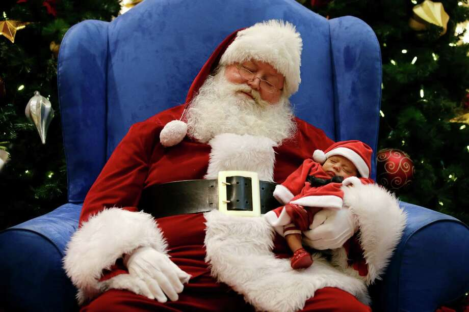 Dressed as Santa Claus, Mark Tate pretends to sleep as he poses for photos with 4-week-old Leilani Mejico at a mall in Cerritos, Calif. on Tuesday, Dec. 17, 2013. Photo: Jae C. Hong, Associated Press / AP